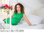 Купить «Attractive woman in dress poses on white bed with pillows in cozy bedroom», фото № 28170809, снято 20 ноября 2015 г. (c) Losevsky Pavel / Фотобанк Лори