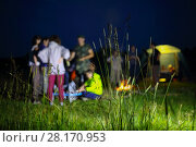 Купить «People stand near fire and tent at night during hike at nature, focus on grass», фото № 28170953, снято 1 июля 2016 г. (c) Losevsky Pavel / Фотобанк Лори