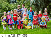 Купить «Group portrait of fifteen children dressed in bright dance suits posing at grassy lawn», фото № 28171053, снято 10 сентября 2016 г. (c) Losevsky Pavel / Фотобанк Лори