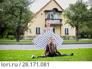 Купить «Smiling boy sits on side split and girl in polka-dotted dress stands behind him on grassy lawn against two-storied house», фото № 28171081, снято 10 сентября 2016 г. (c) Losevsky Pavel / Фотобанк Лори