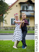 Купить «Boy and girl in dancing suits dance on grassy lawn against two-storied house», фото № 28171085, снято 10 сентября 2016 г. (c) Losevsky Pavel / Фотобанк Лори