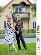 Купить «Boy and girl in dancing suits dance on grassy lawn against two-storied house», фото № 28171089, снято 10 сентября 2016 г. (c) Losevsky Pavel / Фотобанк Лори