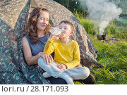 Купить «Happy woman looks at her little son drinking water near tent outside at summer day», фото № 28171093, снято 2 июля 2016 г. (c) Losevsky Pavel / Фотобанк Лори