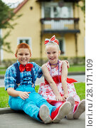 Купить «Smiling boy and girl in bright dancing suits sit on road curb against two-storied house», фото № 28171109, снято 10 сентября 2016 г. (c) Losevsky Pavel / Фотобанк Лори