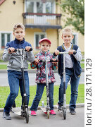 Купить «Two boys and girl stand with push scooters on road against two-storied house», фото № 28171129, снято 10 сентября 2016 г. (c) Losevsky Pavel / Фотобанк Лори