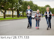 Купить «Two boys and girl ride on push scooters on road», фото № 28171133, снято 10 сентября 2016 г. (c) Losevsky Pavel / Фотобанк Лори