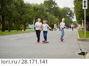 Купить «Two boys and girl ride skateboard and walk on street», фото № 28171141, снято 10 сентября 2016 г. (c) Losevsky Pavel / Фотобанк Лори