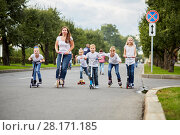 Купить «Woman and five children on scooters, roller skates and skateboard ride on street», фото № 28171185, снято 10 сентября 2016 г. (c) Losevsky Pavel / Фотобанк Лори