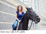 Купить «Young woman on horseback on road at residential complex», фото № 28171205, снято 5 июля 2016 г. (c) Losevsky Pavel / Фотобанк Лори