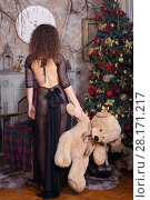 Купить «Woman in transparent dress poses near Christmas fir tree and fireplace with big bear, back view», фото № 28171217, снято 27 ноября 2015 г. (c) Losevsky Pavel / Фотобанк Лори
