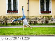 Купить «Girl turns cartwheel on grassy lawn in front of house», фото № 28171229, снято 10 сентября 2016 г. (c) Losevsky Pavel / Фотобанк Лори