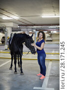 Купить «Young woman with horse at underground parking», фото № 28171245, снято 5 июля 2016 г. (c) Losevsky Pavel / Фотобанк Лори