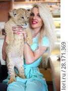 Купить «Beautiful woman smiles and holds funny calf of lion at table in cafe, focus on animal», фото № 28171369, снято 13 июля 2016 г. (c) Losevsky Pavel / Фотобанк Лори