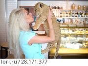 Купить «Beautiful woman kisses funny little calf of lion near showcase in cafe», фото № 28171377, снято 13 июля 2016 г. (c) Losevsky Pavel / Фотобанк Лори