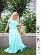 Blonde in long dress sits with calf of lion and strokes it outdoor at summer. Стоковое фото, фотограф Losevsky Pavel / Фотобанк Лори