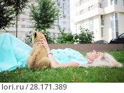 Купить «Blonde with calf of lion lies on grass near building at summer day», фото № 28171389, снято 13 июля 2016 г. (c) Losevsky Pavel / Фотобанк Лори