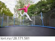 Купить «Beautiful happy woman jumps on trampoline outdoor at summer», фото № 28171581, снято 18 сентября 2016 г. (c) Losevsky Pavel / Фотобанк Лори