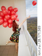 Купить «Young smiling red-haired woman holds in hand bunch of red balloons and leaves one to fly standing at balcony of highrise building», фото № 28171589, снято 15 октября 2015 г. (c) Losevsky Pavel / Фотобанк Лори