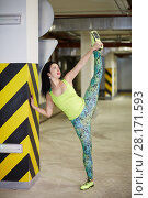 Купить «Young smiling woman does stretching exercise in underground parking», фото № 28171593, снято 15 октября 2015 г. (c) Losevsky Pavel / Фотобанк Лори
