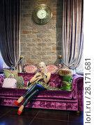 Купить «Blonde beautiful woman sits on purple couch with big snake in room», фото № 28171681, снято 18 июля 2016 г. (c) Losevsky Pavel / Фотобанк Лори