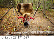 Купить «Woman poses under animal skins drying on wooden stakes in Chukchi camp in autumn forest», фото № 28171697, снято 18 октября 2015 г. (c) Losevsky Pavel / Фотобанк Лори