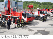 Купить «RUSSIA, MOSCOW - MAY 29, 2015: Fire trucks, fire engine with crane and motorcycles stand on territory of fire station», фото № 28171777, снято 29 мая 2015 г. (c) Losevsky Pavel / Фотобанк Лори