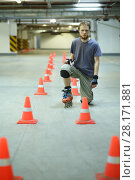 Купить «Roller skater poses on floor near orange cones in empty underground parking», фото № 28171881, снято 22 октября 2015 г. (c) Losevsky Pavel / Фотобанк Лори