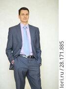 Купить «Handsome brunet man in business suit with tie poses in studio», фото № 28171885, снято 28 апреля 2016 г. (c) Losevsky Pavel / Фотобанк Лори