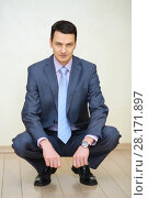 Купить «Handsome man in business suit with tie squats on floor in studio», фото № 28171897, снято 28 апреля 2016 г. (c) Losevsky Pavel / Фотобанк Лори