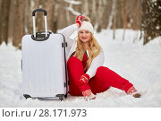 Купить «Young smiling woman sits near trolley bag, propping head with hand in winter park», фото № 28171973, снято 15 января 2016 г. (c) Losevsky Pavel / Фотобанк Лори