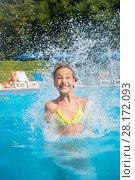 Купить «Happy girl jumps into pool with many splashes outdoor in yard of hotel», фото № 28172093, снято 27 июля 2016 г. (c) Losevsky Pavel / Фотобанк Лори
