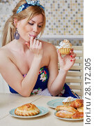 Купить «Young woman in flowery dress sits at table holding homemade cupcake and licking finger at kitchen», фото № 28172205, снято 19 января 2016 г. (c) Losevsky Pavel / Фотобанк Лори