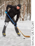 Купить «Alone hockey player going to slash puck at outdoor skating rink», фото № 28172241, снято 21 января 2016 г. (c) Losevsky Pavel / Фотобанк Лори