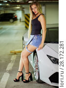 Купить «Showy young woman stands leaning back to modern white car at underground parking», фото № 28172281, снято 2 июня 2016 г. (c) Losevsky Pavel / Фотобанк Лори