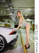 Купить «Young blonde woman in striped bodysuit and high-heel shoes poses leaning hands on trunk of modern white car at underground parking», фото № 28172345, снято 2 июня 2016 г. (c) Losevsky Pavel / Фотобанк Лори
