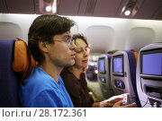 Купить «Man and woman switch channels on display on seat in airplane before flight, focus on man», фото № 28172361, снято 1 ноября 2015 г. (c) Losevsky Pavel / Фотобанк Лори