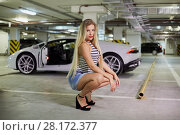 Купить «Young smiling blonde woman in striped bodysuit, jeans overall and high-heel shoes poses sitting squatted against modern white car at underground parking», фото № 28172377, снято 2 июня 2016 г. (c) Losevsky Pavel / Фотобанк Лори