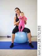 Купить «Happy mother with baby sitting on the big blue ball in the gym», фото № 28172393, снято 5 октября 2016 г. (c) Losevsky Pavel / Фотобанк Лори