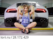 Купить «Young woman in striped bodysuit, jeans overall and high-heel shoes sits on yellow pipe at back of modern white car at underground parking», фото № 28172429, снято 2 июня 2016 г. (c) Losevsky Pavel / Фотобанк Лори