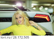 Купить «Young smiling woman in yellow dress sits leaning back onto trunk of modern white car at underground parking», фото № 28172505, снято 2 июня 2016 г. (c) Losevsky Pavel / Фотобанк Лори