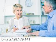 calm mature couple at table attentively study documents. Стоковое фото, фотограф Яков Филимонов / Фотобанк Лори