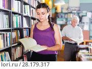 Купить «Young woman is choosing novel for buying», фото № 28179317, снято 28 июня 2017 г. (c) Яков Филимонов / Фотобанк Лори