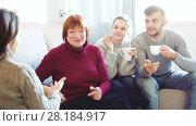 Купить «Portrait of happy family enjoying conversation over cup of coffee at home», видеоролик № 28184917, снято 20 декабря 2017 г. (c) Яков Филимонов / Фотобанк Лори
