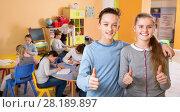 Купить «Two satisfied children standing in schoolroom on background with pupils studying», фото № 28189897, снято 28 января 2018 г. (c) Яков Филимонов / Фотобанк Лори