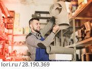 Купить «Young man worker examining plastic drain pipes», фото № 28190369, снято 15 марта 2017 г. (c) Яков Филимонов / Фотобанк Лори
