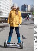 Купить «Девочка в желтой куртке катается на гироскутере», фото № 28191681, снято 17 марта 2018 г. (c) Кекяляйнен Андрей / Фотобанк Лори