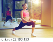 Купить «smiling woman stretching leg in gym», фото № 28193153, снято 29 июня 2014 г. (c) Syda Productions / Фотобанк Лори
