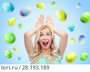 Купить «happy woman making bunny ears over easter eggs», фото № 28193189, снято 13 февраля 2016 г. (c) Syda Productions / Фотобанк Лори