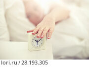 Купить «close up of woman with alarm clock in bed at home», фото № 28193305, снято 30 апреля 2016 г. (c) Syda Productions / Фотобанк Лори