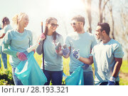 volunteers with garbage bags cleaning park area. Стоковое фото, фотограф Syda Productions / Фотобанк Лори